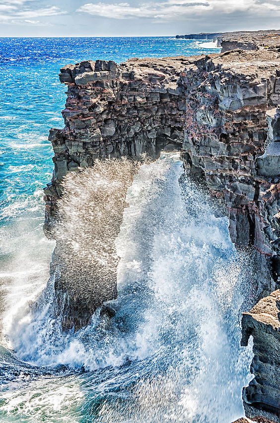 The Holei Sea Arch, formed by lava flows and wave action such as that seen here, located on the south coast of the Big Island of Hawaii in Hawaii Volcanoes National Park.