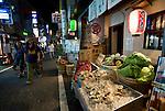 People walk past Kaminari-ya izakaya restaurant located on the main shopping street of central Shimokitazawa, Setagaya Ward, Tokyo, Japan..Photographer: Robert Gilhooly