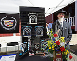 BARTON VT - 144th Orleans County Fair in the scenic Northeast Kingdom village of Barton, Vermont broke the Guinness World Records of the longest Cadillac Parade in history with 298 cars Wednesday in Barton Vermont. Doug Leland, disguised as his relative Henry Leland founder of Cadillac, poises next to the Cadillac Parade trophies at the Orleans County Fairgrounds. .