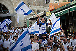 © Joel Goodman - 07973 332324 . 05/06/2016 . Jerusalem , Israel . Thousands of Jews with flags process through Damascus Gate , through the Old City's Muslim district , on the way to the Western Wall , separated from residents of the Old City's Muslim district by Israeli soldiers . Israeli Jews celebrate Jerusalem Day . Photo credit : Joel Goodman