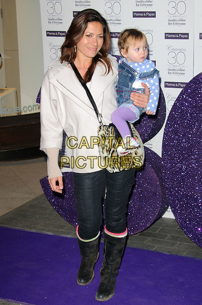 CLARE NASIR & SIENNA.The Mamas & Papas 30th Anniversary Party, Mamas & Papas store, Regent Street, London, England, UK,.March 7th 2011.full length coat jacket jeans denim tucked into boots carrying child kid infant mother mom mum family daughter blue polka dot purple tights black fur collar .CAP/CJ.©Chris Joseph/Capital Pictures.