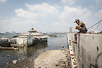 13 August 2019, Jakarta, Indonesia: Local resident Iwan sits on the protective seawall barrier keeping the ocean at bay at Muara Baru, North Jakarta. Built by Governor (now President) Joko Widodo it was constructed to prevent further encroachment by the ocean into the settlements in North Jakarta which is sinking at a rate faster than anywhere else in the world. Residents speak of the flooding  that would drive them to higher ground washing away all in its path. Residents now say the land is dry and usable but it is an ongoing crisis for Indonesia. Picture by Graham Crouch/The Telegraph