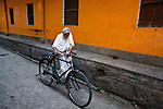 An old man walks with his bicycle through the narrow alleys of Varanasi, Uttar Pradesh, India.