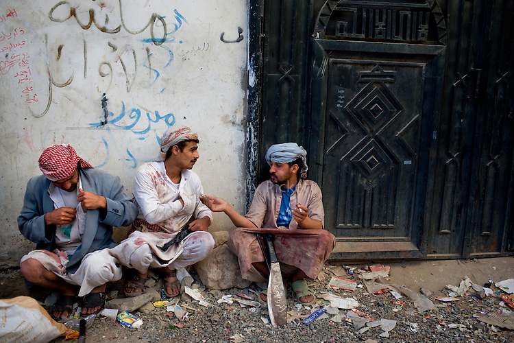 Their clothes blood-stained from the slaughter of sheep for the Muslim holiday Eid al-Adha, men take a cigarette break in the village of Haddah Medina, Yemen, Nov. 27, 2009. A raging conflict with Houthi rebels in Yemen's north and clashes with separatists in the South continue to erode stability in the Arabian Peninsula's poorest state, where half of the population lives in abject poverty.