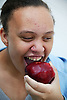 Portrait of a teenage girl eating an apple,