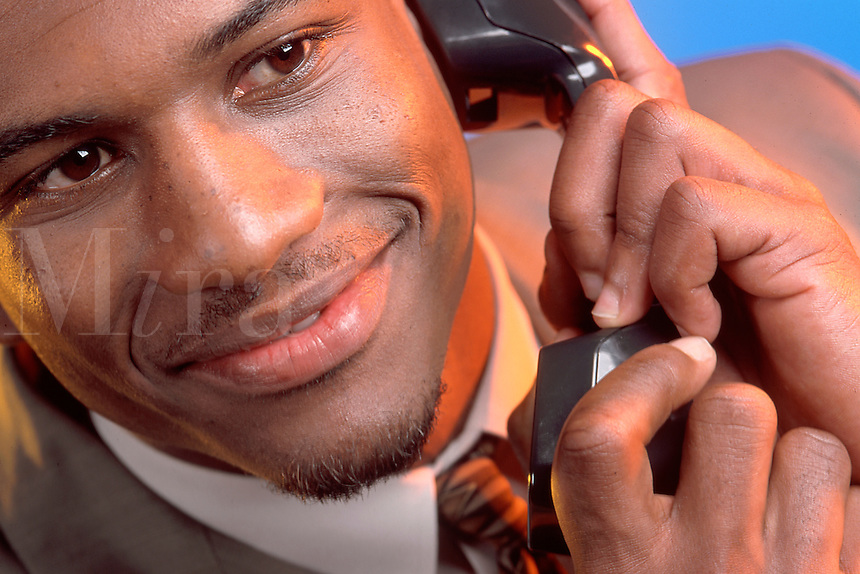 A smiling African American man talking on the telephoone.