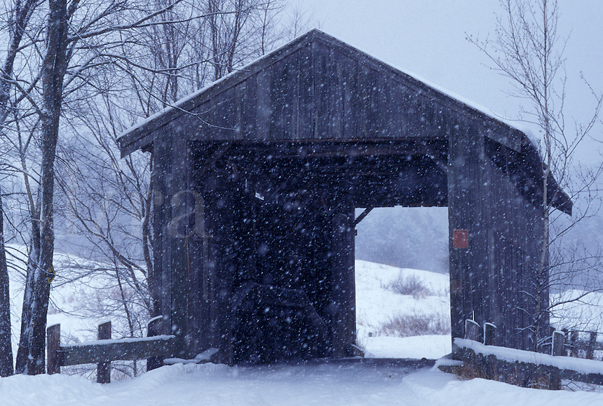 AJ4692, winter, covered bridge, Vermont, Snow falls on Scribner or Mudget Covered Bridge on a snowy wintry in Johnson in Lamoille County in the state of Vermont.
