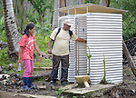Heidi Ramos, the village captain, discusses with Robert Baligira, an advisor to Norwegian Church Aid, a temporary latrine that was built in her village of Cambayan in the Philippines province of Samar, shortly after the region was ravaged by Typhoon Haiyan in November 2013. Known locally as Yolanda, the storm left much of the community's infrastructure a shambles. Norwegian Church Aid, a member of the ACT Alliance, is helping the community rehabilitate its potable water system as well as build new permanent toilets.