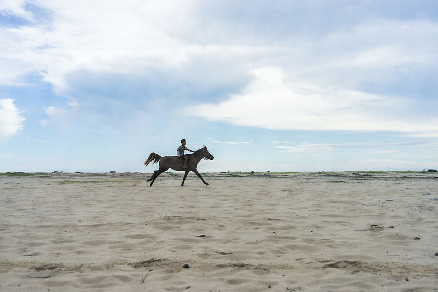March 24, 2016 - Wainyapu (Indonesia). A kid rides a horse on the beach in front of Wainyapu. The remote village is situated along the west coast of Sumba island, and is one of the location of the centuries-old harvest festival known as Pasola. <br /> The festival involves two teams of men on horseback charging towards each other while trying to hit their rivals with 'pasol' javelins and avoid being hit themselves. &copy; Thomas Cristofoletti / Ruom