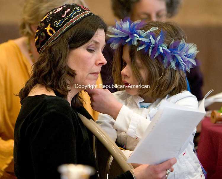 SOUTHBURY, CT- 18 MARCH 07- 031907JT01- <br /> Rachel Barclay follows along to a song in her program while her daughter Anna Pecovich, 6, plays with her hair during a women's seder at the Federation, Jewish Communities of Western Connecticut in Southbury on Sunday, March 18.<br /> Josalee Thrift Republican-American