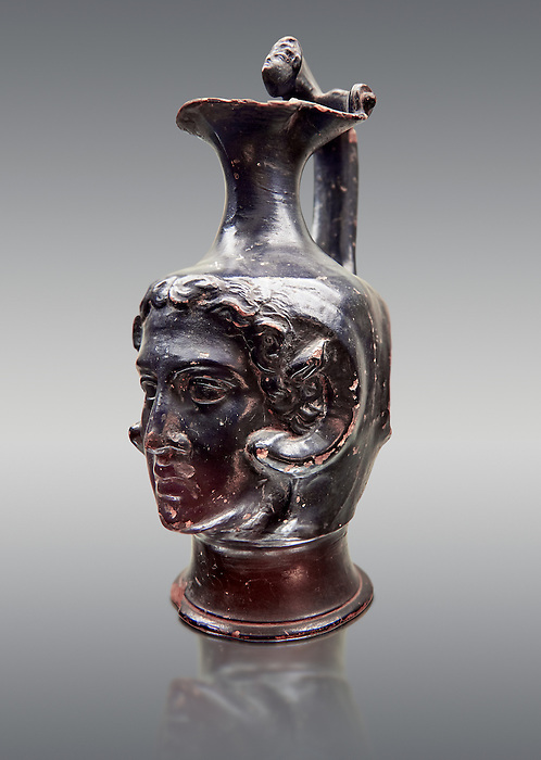 Etruscan bucchero jug with a face,  National Archaeological Museum Florence, Italy , against grey