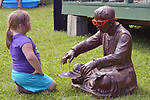 A young listener sits in front of a Zen-Like Statue in front of the Canal Lock Stage, while MAX'S NEW HAT plays during the Rosendale Street Festival of 2017, in Rosendale, NY, on Saturday, July 15, 2017. Photo by Jim Peppler. Copyright/Jim Peppler-2017.