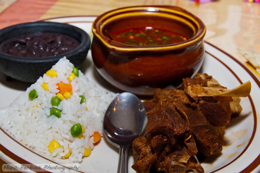 Barbacoa de Chivo, goat cooked in a red chile sauce, at Casa Oaxaca in Santa Ana, CA.  The goat was delicious and meaty tasting.  The rice and beans were both excellent, but the start of the meal was the goat consome: it had a pure meat flavor, and was incredibly well spiced.