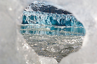 Monaco Glacier viewed through hole of ice berg stranded on shore, West Svalbard, Norway
