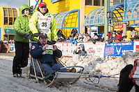 Ken Anderson and team leave the ceremonial start line with an Iditarider at 4th Avenue and D street in downtown Anchorage, Alaska during the 2015 Iditarod race. Photo by Jim Kohl/IditarodPhotos.com