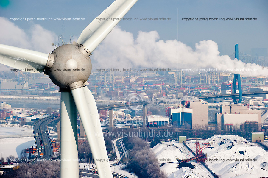 GERMANY Hamburg , Enercon windmill E-126 with 6 MW during Winter, to the right snow covered coal and ore port Hansaport, skyline of Hamburg during winter / Deutschland Hamburg , Enercon Windrad E-126 mit 6 MW in Altenwerder,  Hintergrund Hafen, Koehlbrandbruecke und city skyline im Winter, rechts schneebedeckter Hansaport Kohle und Erz Hafen