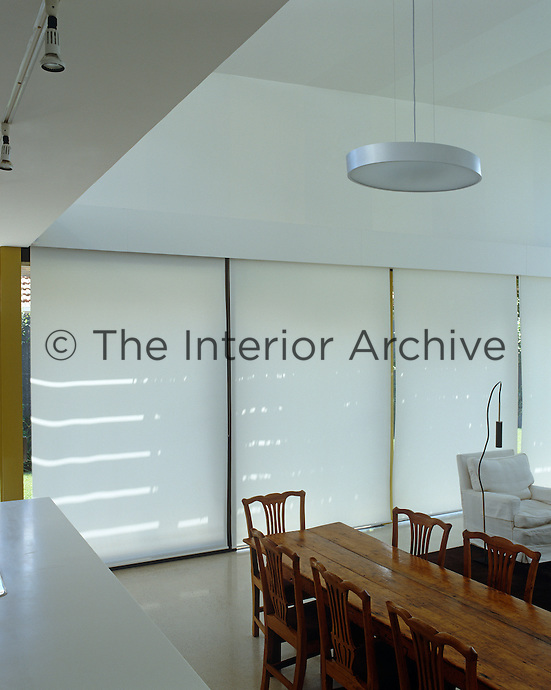 Opaque white blinds in this open plan living area help to maintain an even temperature
