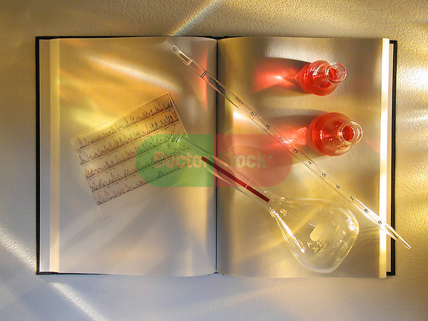 still-life of journal with EKG graph, medical glassware, pipette, flask