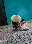A woman counts her money on a sidewalk in District 1 in Ho Chi Minh City, Vietnam. Aug. 24, 2011.