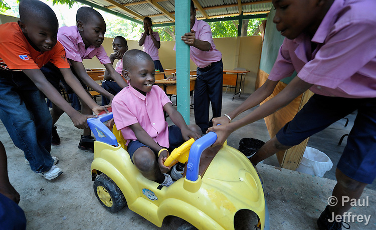 A boy gets to drive with some help from his friends in the Foyer d'Amour d'Haiti, an Orthodox Church-sponsored school for mentally challenged children in the Fontamara neighborhood of Port-au-Prince, Haiti..
