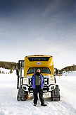 USA, Wyoming, Yellowstone National Park, portrait of a Yellowstone guide standing in front of a Snowcoach on the road between Mammoth Hot Springs and Norris