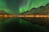 Northern lights reflect in calm fjord at Skjelfjord, Flakstadøy, Lofoten Islands, Norway