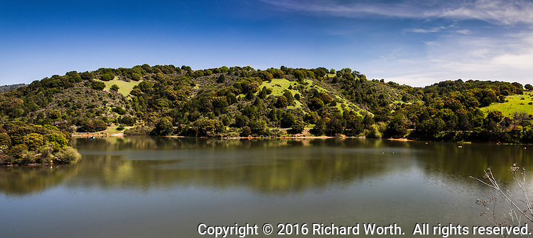 A panoramic view of Lake Chabot's east shore with blue skies over green rolling hills covered in trees and grass and all reflected in the lake.