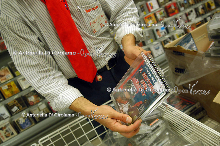 Supermercato Coop. Coop supermarket..Commesso aziona il sistema antitaccheggio ai dvd..Sales assistant operates the antitheft system to the dvd....