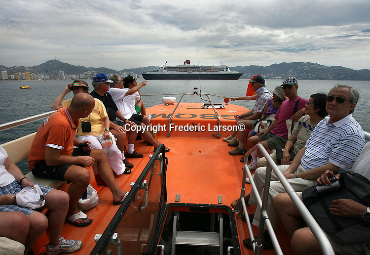 Passengers return to the Queen Mary 2 from visiting the town of Acapulco for an afternoon before they sailing out this evening north to San Francisco, California.