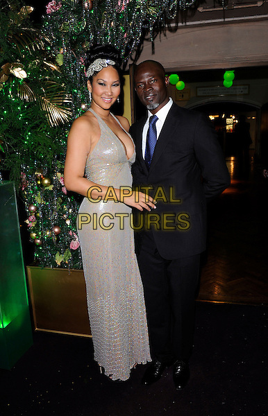 KIMORA LEE SIMMONS & DJIMON HOUNSOU.at The Emerald Ball In Aid Of The Elton John Aids Foundation, Harrods, London, England, November 5th, 2009..full length couple silver dress headband hairband hair head band blue tie black suit white shirt sequins sequined cleavage hand long maxi .CAP/FIN.©Steve Finn/Capital Pictures