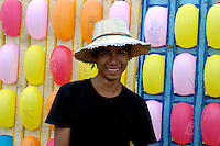 Carnival Time During the annual boat races in Phnom Penh Cambodia, festivities are held, like trowing darts at these colorful balloons, for a small prize.The poor peoples entertainment