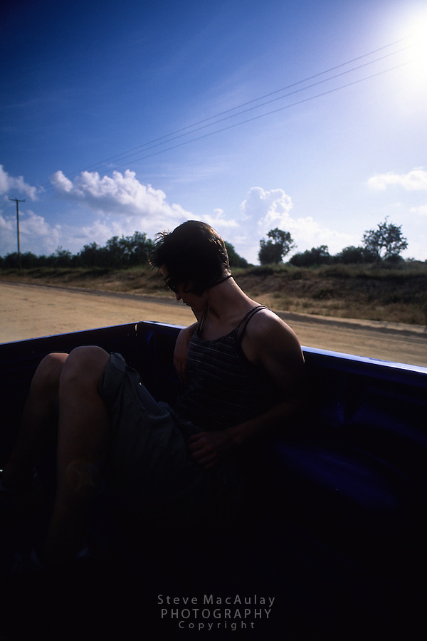 Female traveler riding in the back of a open pickup truck on a dusty road, Belize