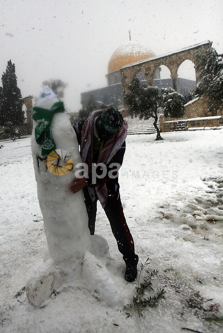 A Palestinian man builds a Hamas handmade M75 rocket by snow at the Al-Aqsa mosque compound in the old city of Jerusalem on January 10, 2013. Jerusalem was transformed into a winter wonderland after heavy overnight snowfall turned the Holy City and much of the region white, bringing hordes of excited children onto the streets. Photo by Mahfouz Abu Turk