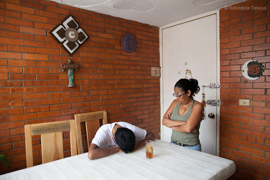 """Baruch lies on the table as his mother looks on, at his home in the Iztapalapa area of Mexico City, Mexico on July 23, 2014. Lately pain related to his cancer has made ordinary tasks very difficult for him. Baruch Alejandro Anleu Ramirez, 18, is the captain of Guerreros Aztecas. Two years ago, Baruch had his left leg amputated due to bone cancer. He used to practice as much as his chemotherapy would allow. Expelled from school for missing too many classes during his treatment, he says, """"Guerreros Aztecas has filled a big hole in my life"""". Baruch was Guerreros Aztecas's brightest hope to represent Mexico at the Amputee Soccer World Cup. But since the cancer's spread to his lungs, he can no longer play or train with the team. Guerreros Aztecas (""""Aztec Warriors"""") is Mexico City's first amputee football team. Founded in July 2013 by five volunteers, they now have 23 players, seven of them have made the national team's shortlist to represent Mexico at this year's Amputee Soccer World Cup in Sinaloathis December.The team trains twice a week for weekend games with other teams. No prostheses are used, so field players missing a lower extremity can only play using crutches. Those missing an upper extremity play as goalkeepers. The teams play six per side with unlimited substitutions. Each half lasts 25 minutes. The causes of the amputations range from accidents to medical interventions – none of which have stopped the Guerreros Aztecas from continuing to play. The players' age, backgrounds and professions cover the full sweep of Mexican society, and they are united by the will to keep their heads held high in a country where discrimination against the disabled remains widespread.(Photo byBénédicte Desrus)"""
