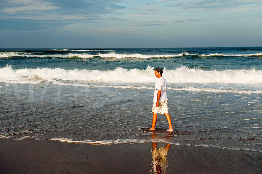 Man taking a relaxing walk along the beach and shallow surf, Nauset Beach, Cape Cod, MA, USA