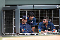 Left fielder Tim Tebow (15) of the Columbia Fireflies, right, talks in the dugout with hitting coach Joel Fuentes, left, and Andres Gimenez in a game against the Greenville Drive on Wednesday, June 14, 2017, at Fluor Field at the West End in Greenville, South Carolina. Columbia won, 6-2, in 11 innings. (Tom Priddy/Four Seam Images)