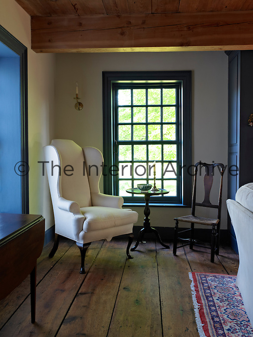In a corner of the living room a Massachusetts tripod table stands beside a George II wing-backed armchair which was recovered in a modern fabric