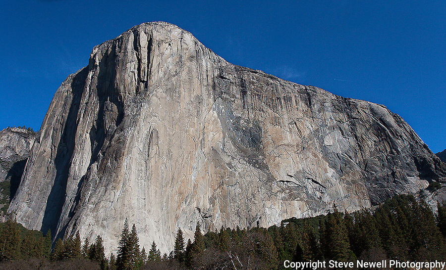 """""""Capitan's Glory"""" Color- El Capitan, Yosemite NP. El Capitan is one of the most spectacular granite monoliths in the world.  Climbers from around the world flock to Yosemite Valley every year for a chance to climb this grand spectacle.  The most famous climbing route on El Capitan is """"The Nose"""".  The route ascends the prow on the sun/shade line to the right of the Heart.  The prominent Heart appears as if was carved into the rock but is a natural formation on El Capitan."""
