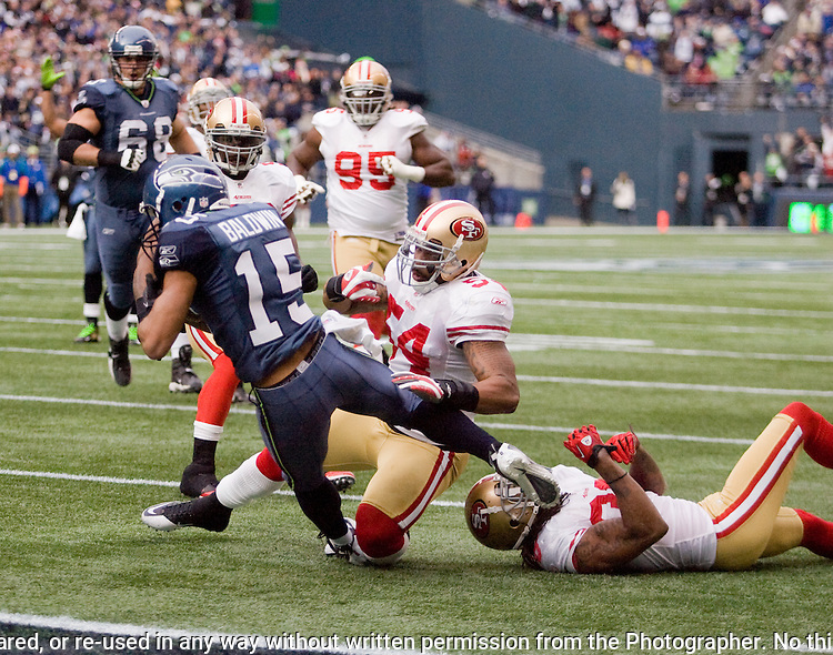 Seattle Seahawks wide receiver Doug Baldwin beaks a tackle by  San Francisco 49ers linebacker Larry Grant and safety Dashon Goldson and scores a 13-yard touchdown at CenturyLink Field in Seattle, Washington on December 24, 2011.  The 49ers came from behind to beat the Seahawks 19-17. ©2011 Jim Bryant Photo. All Rights Reserved.