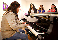 NWA Democrat-Gazette/DAVID GOTTSCHALK Jazmin Chuc (from right), Claudia Rivas and Heidi Sotz, all sophomores at Huntsville High School, listen Tuesday, November 27, 2018, to Yaretze Franco, a freshman, play the piano at the Arts Center of the Ozark in Springdale. The students are members of the International Club at the high school and were seeing the exhibit Frida Kahlo's Garden at the center.