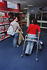 Teenage girl with physical disability using walking frame to walk through college library with friend,