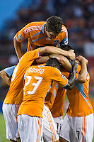 Houston Dynamo defender Bobby Boswell (32) jumps on top of Dynamo players Dominic Oduro (23), Brian Ching (25), and Mike Chabala (17) to celebrate a goal.  Houston Dynamo defeated D.C. United 4-3 at Robertson Stadium in Houston, TX on August 1, 2009.