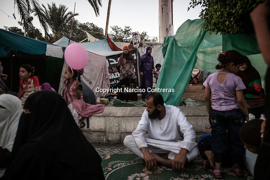 In this Thursday, Aug. 08, 2013 photo, supporters of the ousted president Mohammed Morsi await for the prayers at the dusk in the sit-in of the Cairo University in Giza district. (Photo/Narciso Contreras).