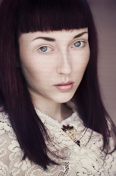 Young female with dark hair, blue eyes, pale skin wearing a white lace top looking at the camera.
