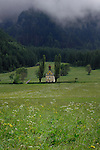Yellow chapel with dome in spring meadows, against background of swirling clouds and forested mountains. Pitztal,Imst district,Tyrol, Austria.