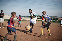 """SOWETO, SOUTH AFRICA - OCTOBER 23: Zacharia """"Computer"""" Lamula, an old football star in the local team Kaizer Chiefs teaches young boys his skills on September 15, 2007 in the Diepkloof section of Soweto, South Africa. Soccer is the most popular sport in South Africa, and a because of the upcoming World Cup 2010, the interest is increasing. For the first time the World Cup will be held on the African continent. South Africa doesn't have an organized youth soccer program and many teams and players struggle with lack of funds to buy equipment and securing money for transport to games. (Photo by Per-Anders Pettersson)....."""