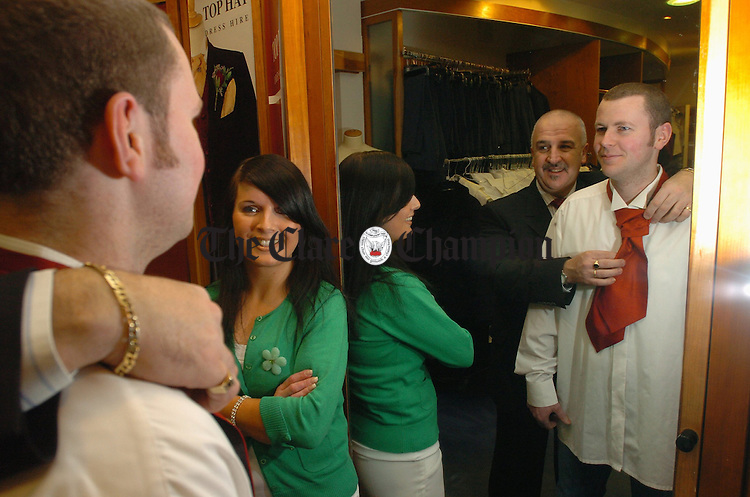 Rio Kelly of Patrick Bourke's menswear tries a crevat on groom to be, Declan Custy from Darragh, watched by his fiancee Ann Molloy from Mayo at the Patrick Bourkes Menswear Wedding fair. Photograph by John Kelly.