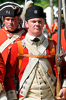 Redcoat soldier of His Majesty's 62nd Regiment of Foot, with characteristic starred pewter cap badge, stands to attention with flintlock musket awaiting orders at a Revolutionary War re-enactment at Fort Ticonderoga, New York, USA.