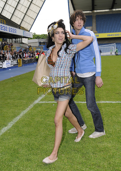 AMY WINEHOUSE.Arrives at the annual Soccer Six charity football match at Millwall Football Club, London, England, 18th May 2008..6 FC full length head scarf beehive blue plaid check shirt denim shorts ballet shoes  brown paper bag pitch.CAP/DH.©David Hitchens/Capital Pictures