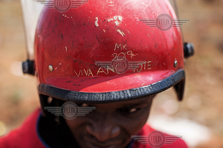 'MK 2019 Viva ANC Vote' - a reference to the African National Congress and it's now disbanded armed wing MK (Umkhonto WeSizwe) and the forthcoming elections in 2019 - is scratched into the helmet of a Red Ant involved in an operation to clear dwellings and evict squatters from land in Vlakfontein. The violent action resulted in the deaths of two people from among the community being evicted. The Red Ants are a controversial private security company often hired to clear squatters from land and so-called 'hijacked' properties.